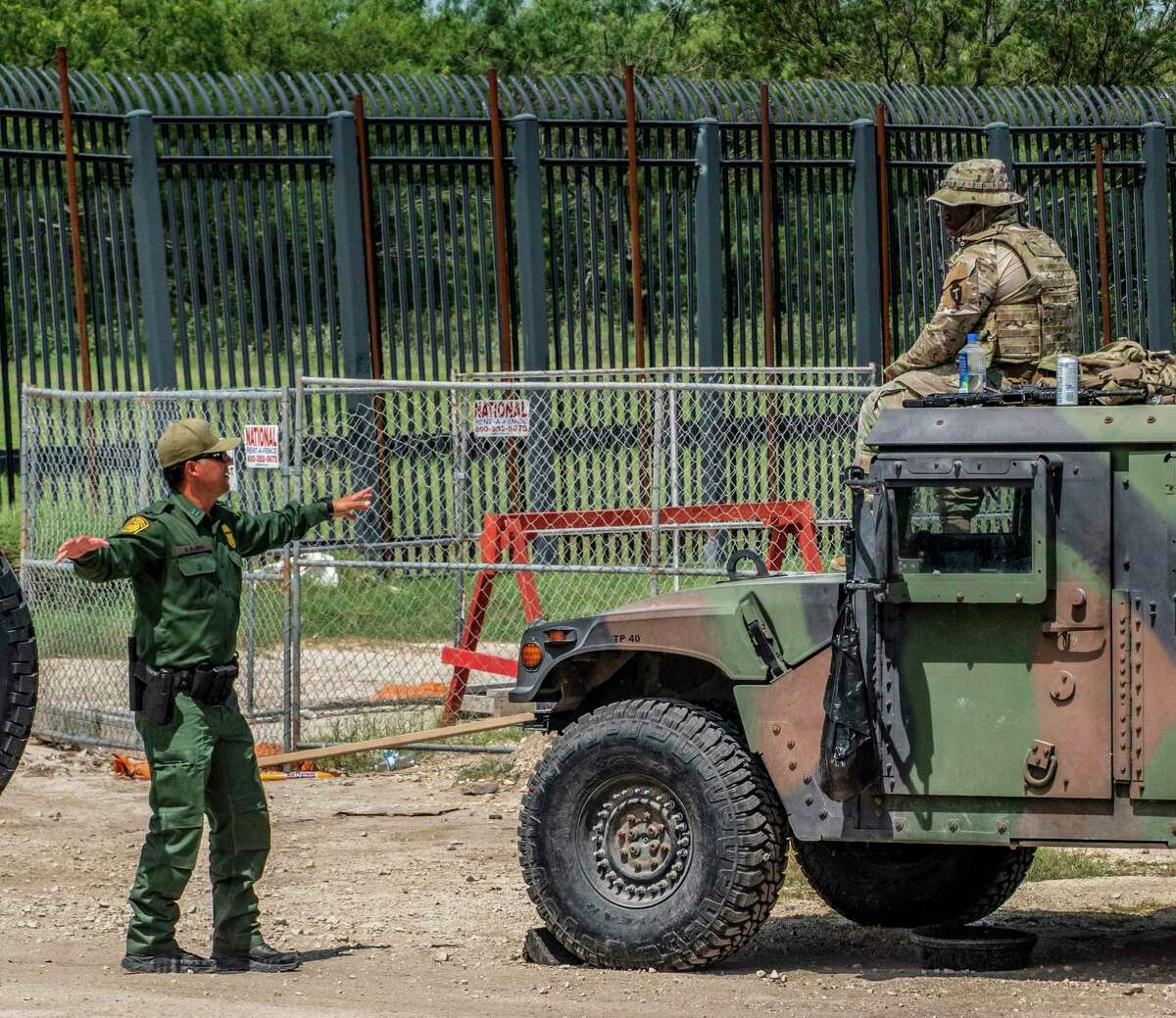 A Border Patrolman, left, speaks with a Texas National Guardsman along the the border fence at Del Rio, Texas, on Tuesday, July 30, 2021. Texas Gov. Greg Abbott has sent the Texas National Guard and Department of Public Safety troopers to stop the migration.