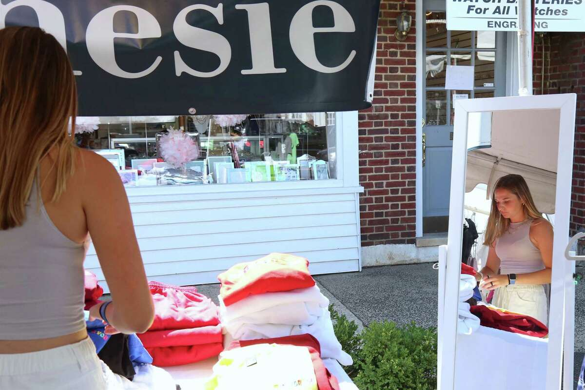 Kelly Palmer of Hanesie reflects a focus on setting up merchandise at the Sidewalk Sales & Family Fun Days event on Saturday, July 31, 2021, in Darien, Conn.