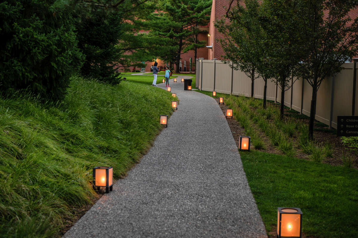 Movie goers walk down the lighted path during an outdoor screening of Disney's Raya and the Last Dragon Saturday, July 30, 2021 at Dow Gardens. (Adam Ferman/for the Daily News)