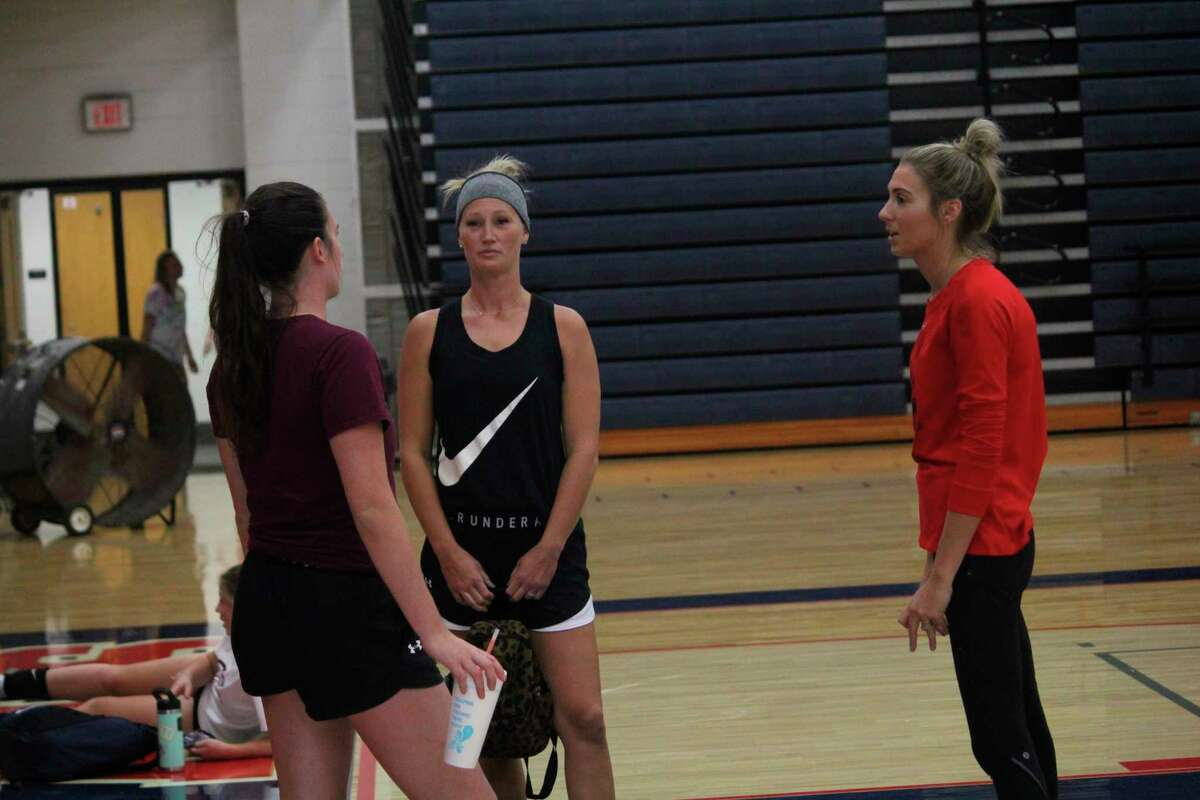 Big Rapids volleyball coach Emily Van Culin (center) discusses Friday's camp along with other attendees including assistant FSU coachHannah Wuest (right).
