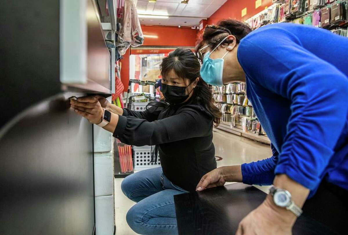GoApple owner Fanly Chen (left) installs a folding platform on the counter inside her phone repair store in San Francisco's Chinatown.