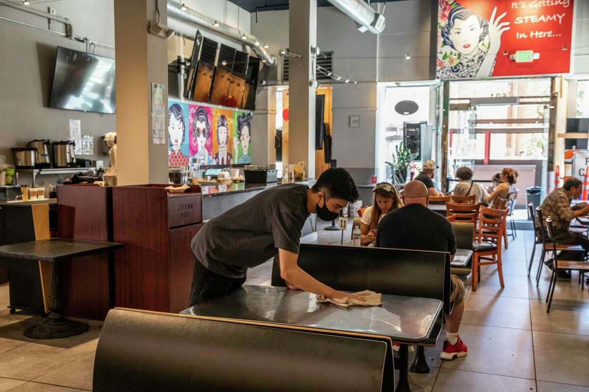 Tyler Chia disinfects a tables inside Dim Sum Corner in San Francisco's Chinatown. It was recently among served with a lawsuit for alleged violation of the Americans with Disabilities Act.