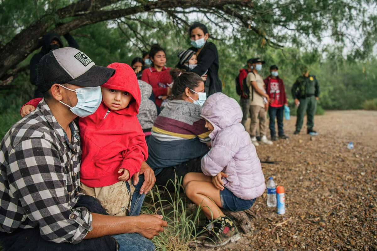 Immigrants seeking asylum wait to be processed by border patrol after crossing into the U.S. on June 16, 2021 in La Joya, Texas. A surge of mostly Central American immigrants crossing into the United States has challenged U.S. immigration agencies along the U.S. Southern border.