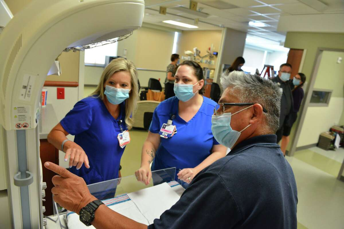 Brandi Carr, Amanda Gregory and Anthony Quiroz look over a new infant warmer during a tour of the newly upgraded Women's Services Unit at Baptist Mission Trail Hospital on July 27, 2021.