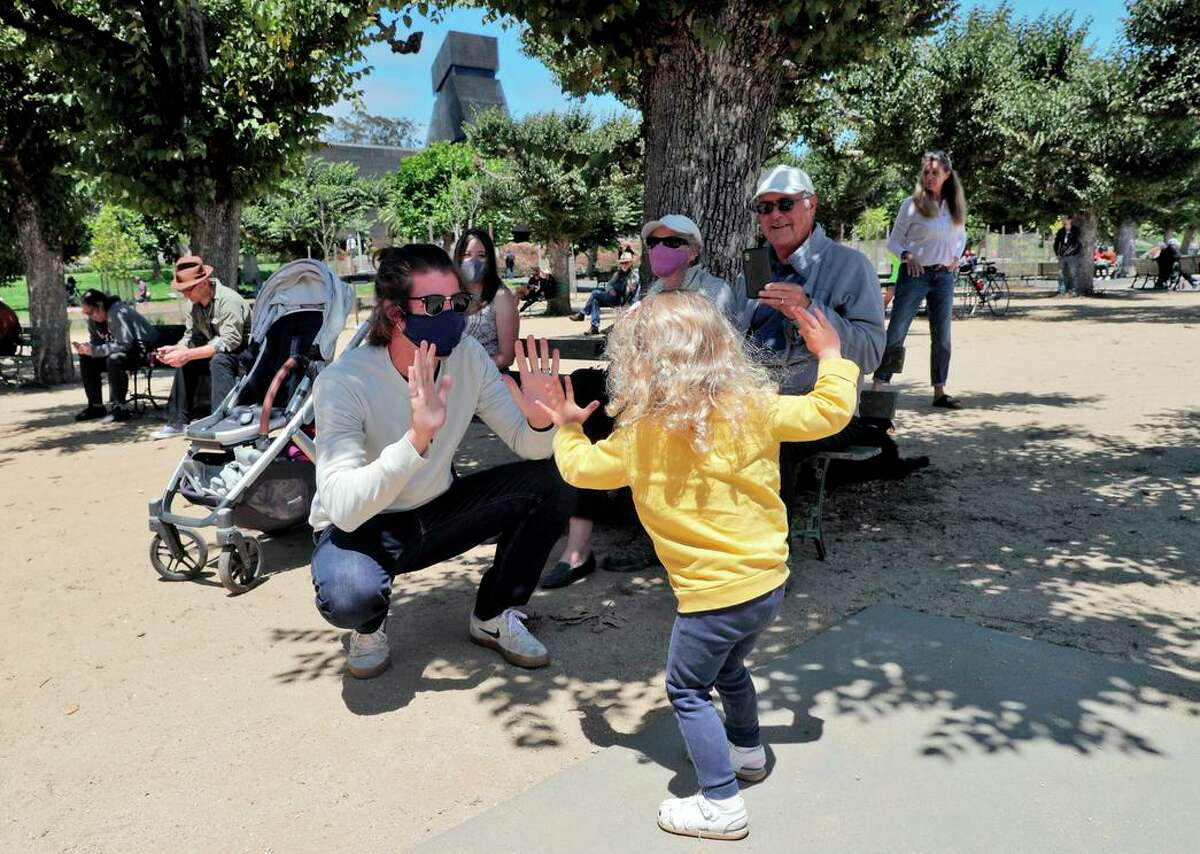 Orla Magee, 2, dances with her father, Riley Magee, as the Golden Gate Park Band performs in San Francisco. The concert was the band's first since October 2019 because of the pandemic.