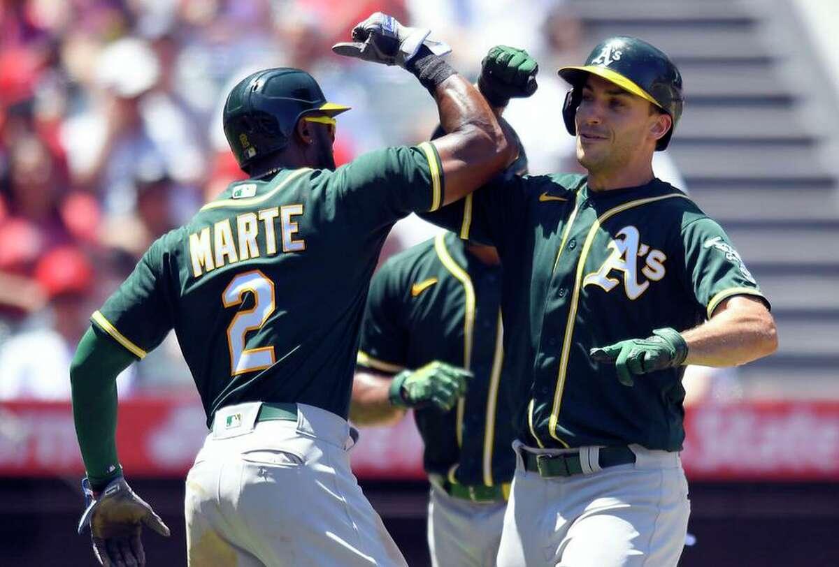 Starling Marte congratulates Matt Olson after Olson's three-run homer in the third inning against the Angels.