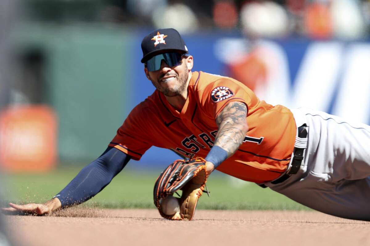 Houston Astros' Carlos Correa dives for a ball hit by San Francisco Giants' Donovan Solano during the eighth inning of a baseball game in San Francisco, Sunday, Aug. 1, 2021. (AP Photo/Jed Jacobsohn)