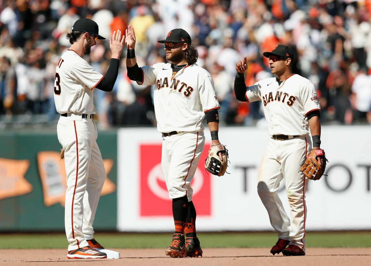 SAN FRANCISCO, CALIFORNIA - AUGUST 01: San Francisco Giants players Kris Bryant #23, Brandon Crawford #35 and Donovan Solano #7 celebrate after a win against the Houston Astros at Oracle Park on August 01, 2021 in San Francisco, California. (Photo by Lachlan Cunningham/Getty Images)