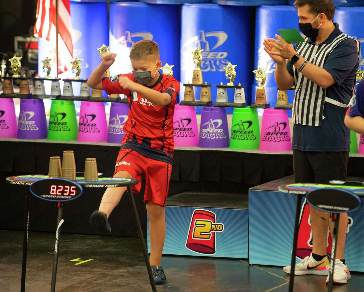 Eleven-year-old Max Jackson, left, of Pennsylvania, reacts as he wins gold in the Special Stacks Stack Out event during the final day of the Sport Stacking tournament in the AAU Junior Olympic Games, Sunday, Aug. 1, 2021, at the George R. Brown Convention Center in Houston. This was Max's second trip to the AAU Junior Olympic Games.