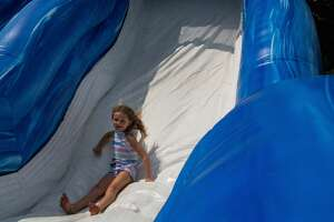 Taliesyn, 7, goes down an inflatable slide on her birthday at Pop Up PaloozaSunday, Aug. 1, 2021 in Sanford's Porte Park. (Drew Travis/for the Daily News)