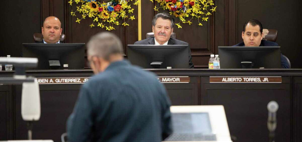 Laredo Mayor Pete Saenz, center, is flanked by councilmembers Ruben Gutierrez Jr. and Alberto Torres Jr. on July 12 at a city council meeting. The City of Laredo announced it will file a lawsuit against Texas Gov. Greg Abbott and the state of Texas regarding their inability to issue a mask mandate amid growing COVID-19 figures on Wednesday night during an emergency council meeting.