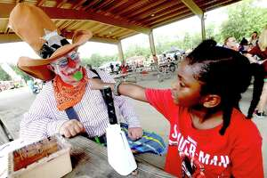 Ti'Shawri Elam checks out the colorful beard of sheriff clown Radar Kelly during the annual Orange County Sheriff's Cops and Kids Picnic Friday in Claiborne Park. Photo made Friday, July 30, 2021 Kim Brent/The Enterprise