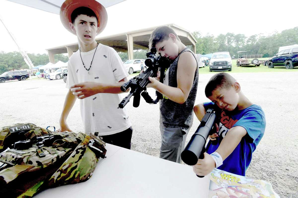 From left, Colton Richard, Austin Hathaway and Ryder Richard check out the guns and grenade launchers used by SWAT team members during the annual Orange County Sheriff's Cops and Kids Picnic Friday in Claiborne Park. Photo made Friday, July 30, 2021 Kim Brent/The Enterprise