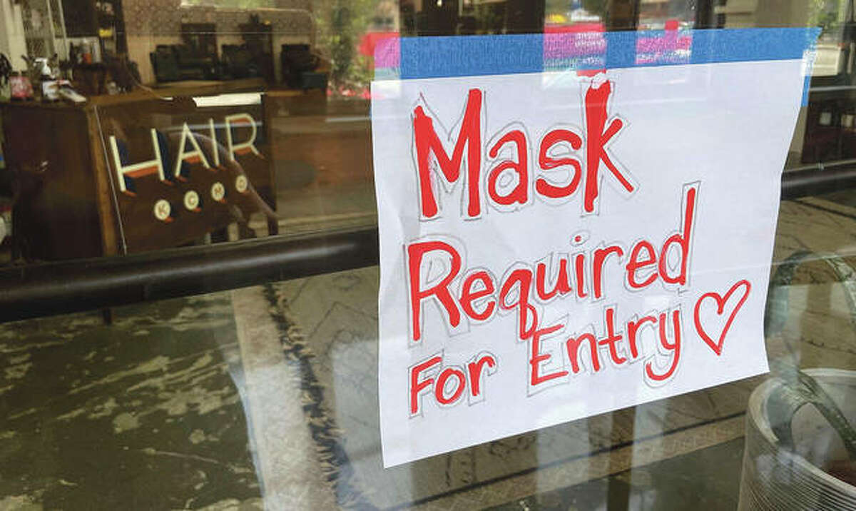 A sign on the door of a hair salon tells patrons that masks are required to be in the business in Missouri. A closer look at data indicates a spillover effect as Illinois regions that share a border with the Show Me State, and where vaccination rates are lower than state average, experience higher rates of infection than other parts of the state.