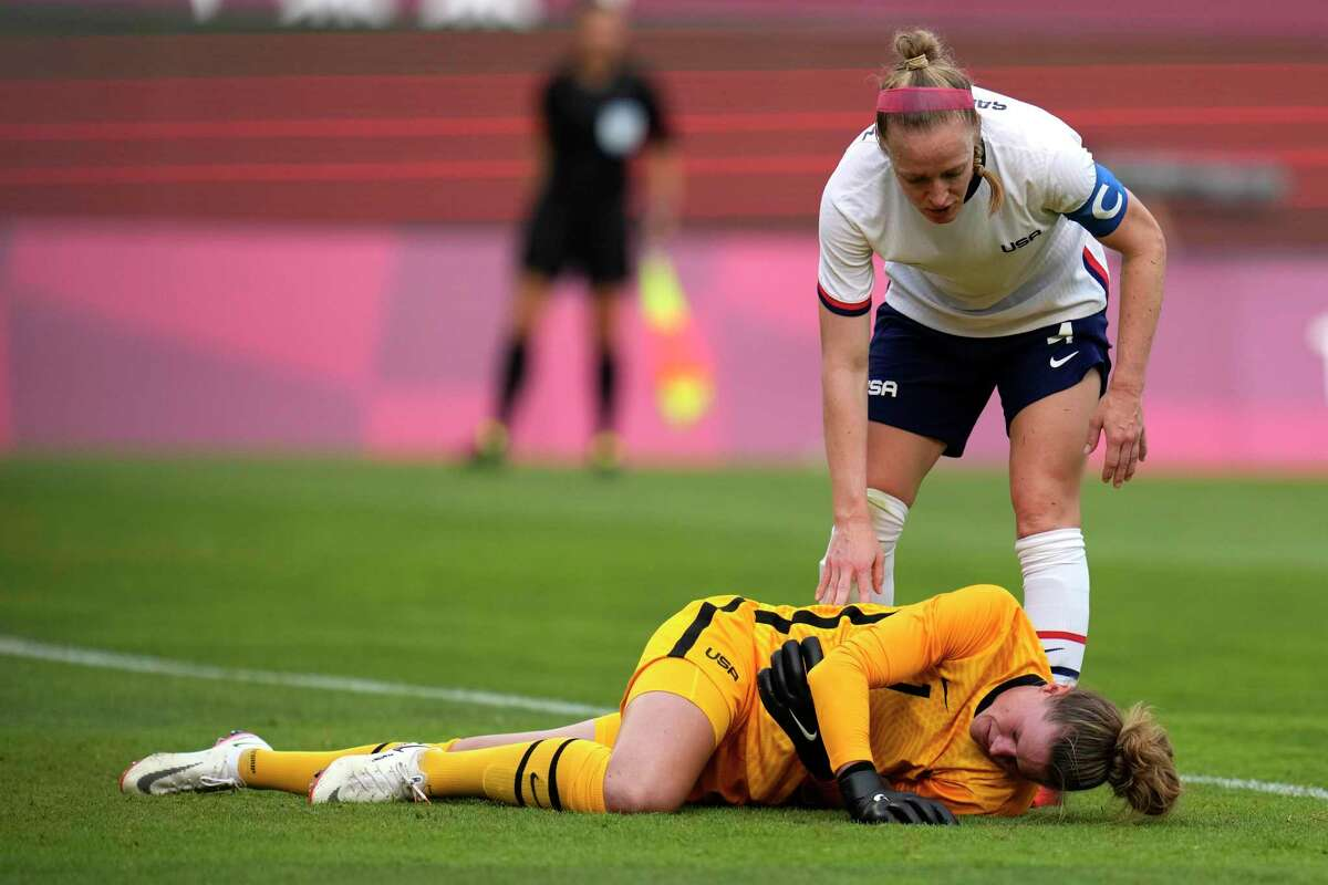 United States' goalkeeper Alyssa Naeher, below, lies on the field during a women's semifinal soccer match against Canada at the 2020 Summer Olympics, Monday, Aug. 2, 2021, in Kashima, Japan.(AP Photo/Fernando Vergara)