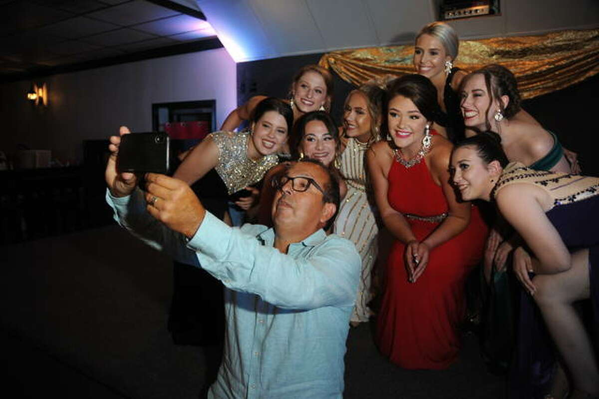 The pageant emcee takes a selfie with the Miss Madison County Fair Queen contestants during Saturday's pageant.
