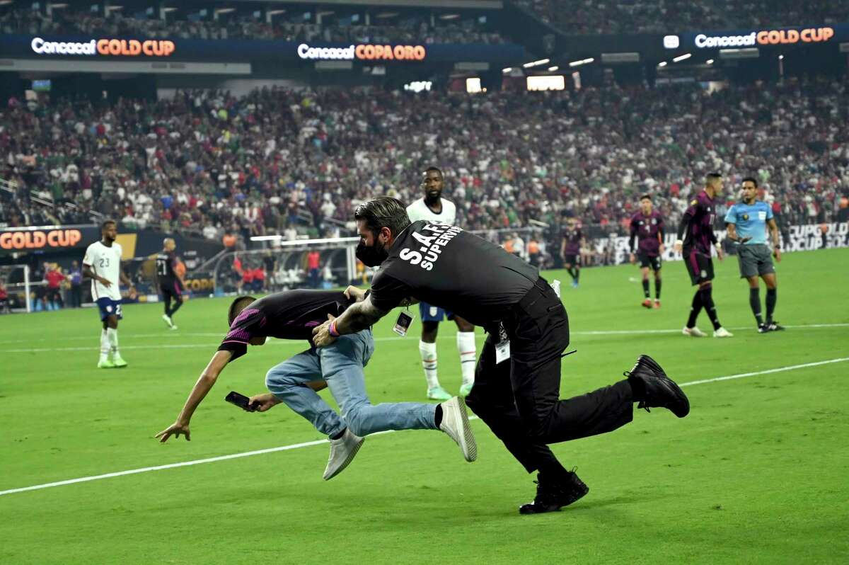 A security guard tackles a spectator who ran on the field during the second half of the CONCACAF Gold Cup final soccer match between United States and Mexico Sunday, Aug. 1, 2021, in Las Vegas. (AP Photo/David Becker)