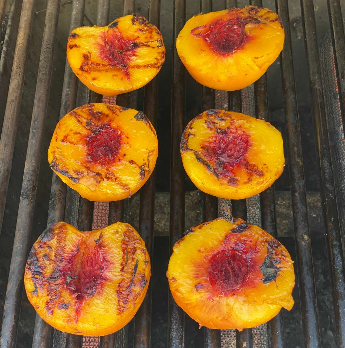 Grilling fresh, juicy summery peaches caramelizes the sugars in the ripe fruit. (Susie Davidson Powell/for the Times Union)