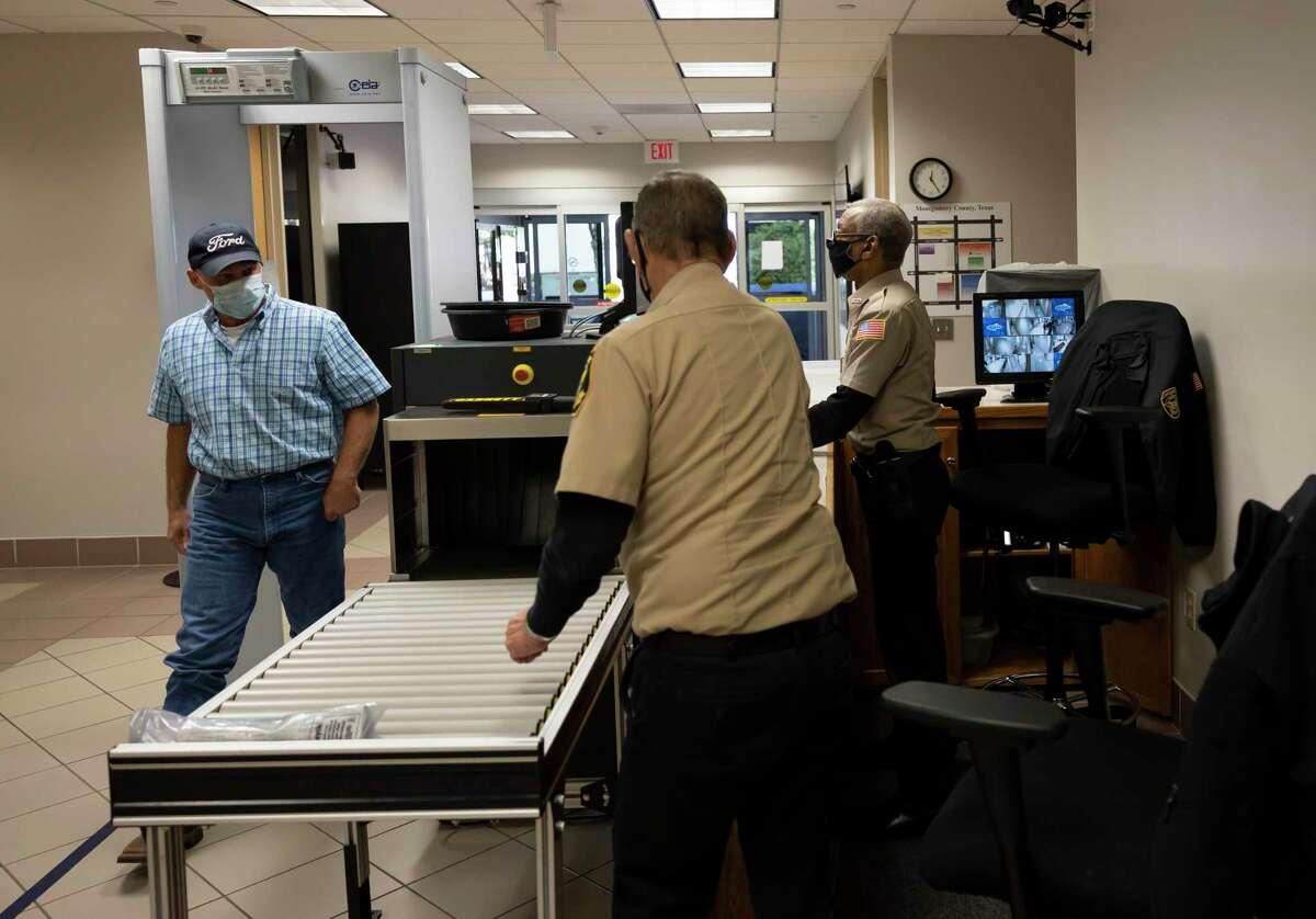 A visitor walks through metal detectors a federal building recently.