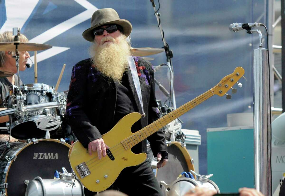FILE - Dusty Hill, of ZZ Top, performs before the start of the NASCAR Sprint Cup series auto race in Concord, N.C., May 24, 2015. ZZ Top has announced that Hill, one of the Texas blues trio's bearded figures and bassist, has died at his Houston home. He was 72. In a Facebook post, bandmates Billy Gibbons and Frank Beard revealed Wednesday, July 28, 2021, that Hill had died in his sleep. (AP Photo/Mike McCarn, File)
