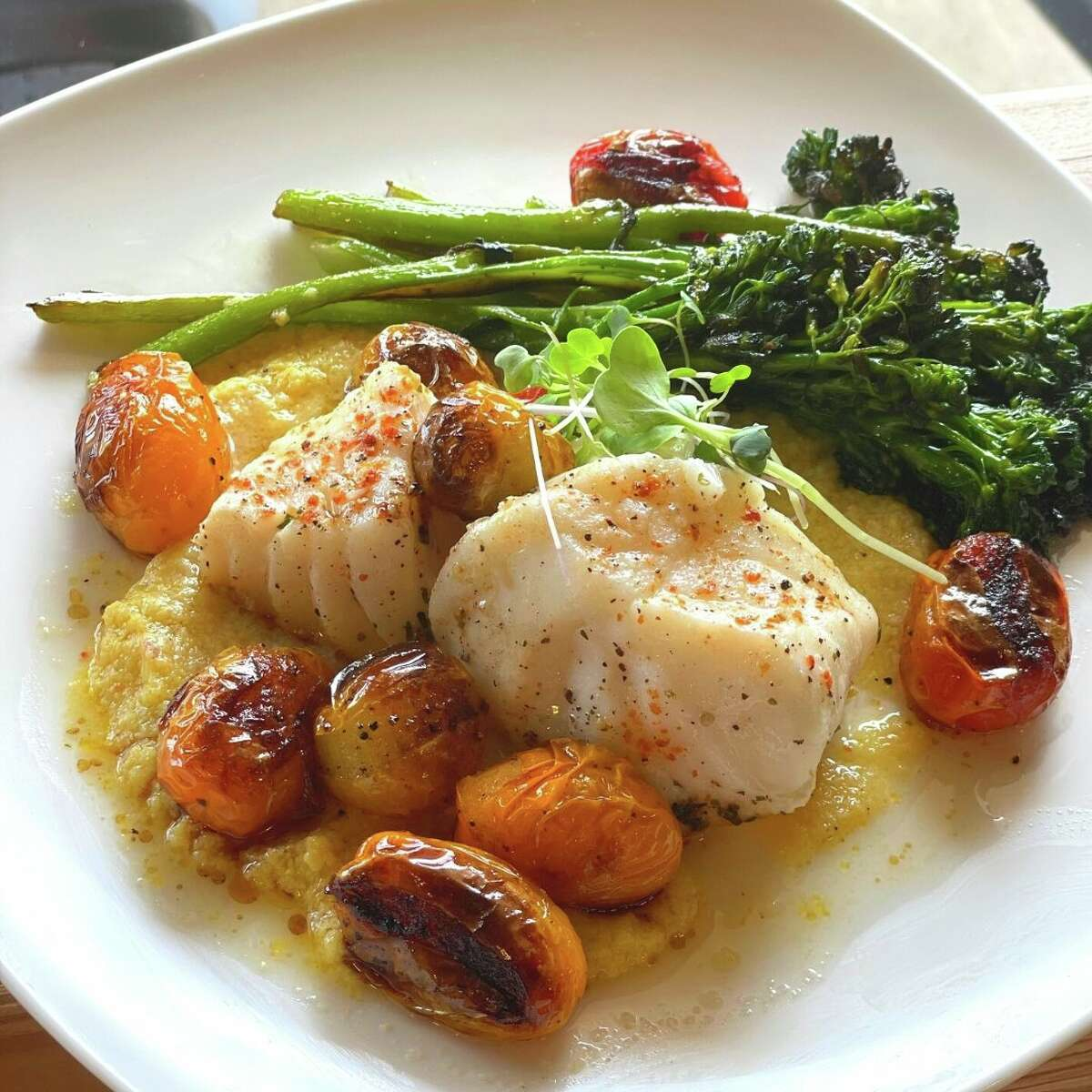 Cod with blistered tomatoes and grilled broccolini is among the dishes being developed for the relocated, expanded Hooked Market & Kitchen in Latham, due to open in mid-August 2021. (Provided photo.)