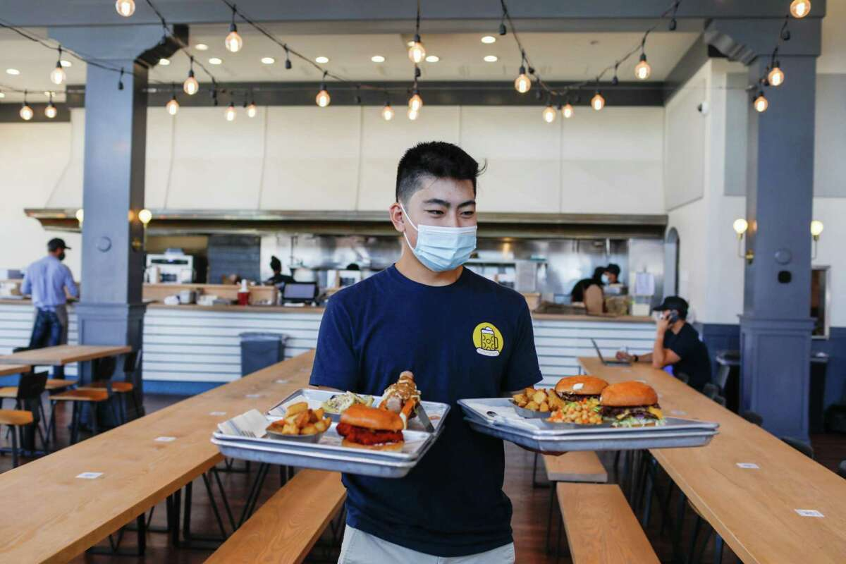Server Brett Kuwahara wears a mask at Wursthall in San Mateo. Seven Bay Area counties have issued an indoor mask mandate to help slow the spread of the delta coronavirus variant.