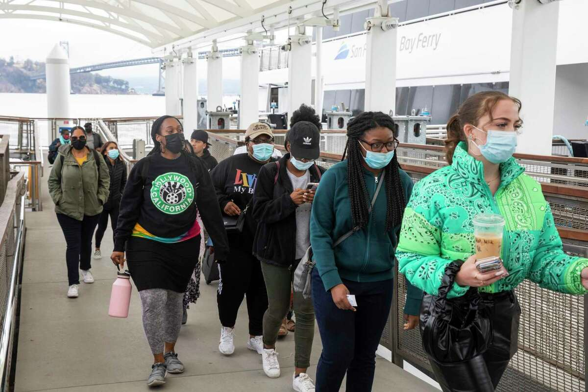 Commuters wear masks while exiting a ferry boat from Vallejo at the ferry terminal in San Francisco.