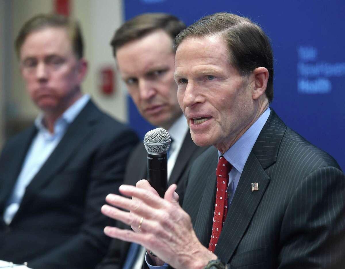 From left, Governor Ned Lamont and U.S. Senator Chris Murphy listen to U.S. Senator Richard Blumenthal, in a 2020 file photo.