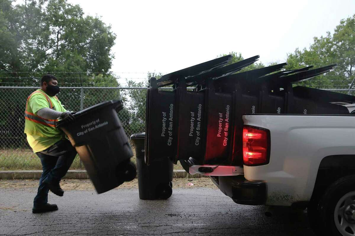 City of San Antonio Solid Waste Management employees pick up trash cans in the Camelot II subdivision of Bexar County on Monday. The city was picking up the trash in the county area but Bexar County recently contracted Tiger Sanitation for trash pickups.