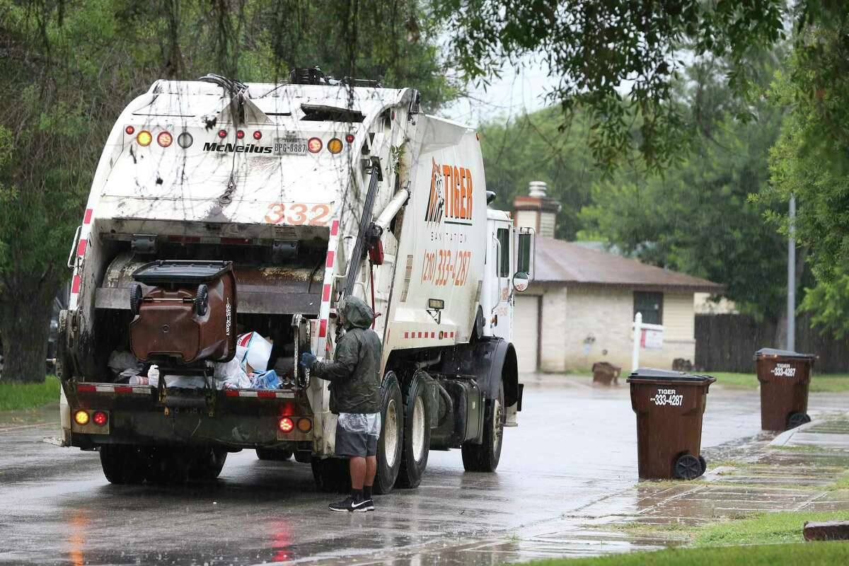 A Tiger Sanitation truck picks up trash in the Camelot II subdivision of Bexar County on Monday. It was the first day of the company's contract with Bexar County to service Camelot and other neighborhoods in the area. Residents are charged a monthly fee of $27 for the service.