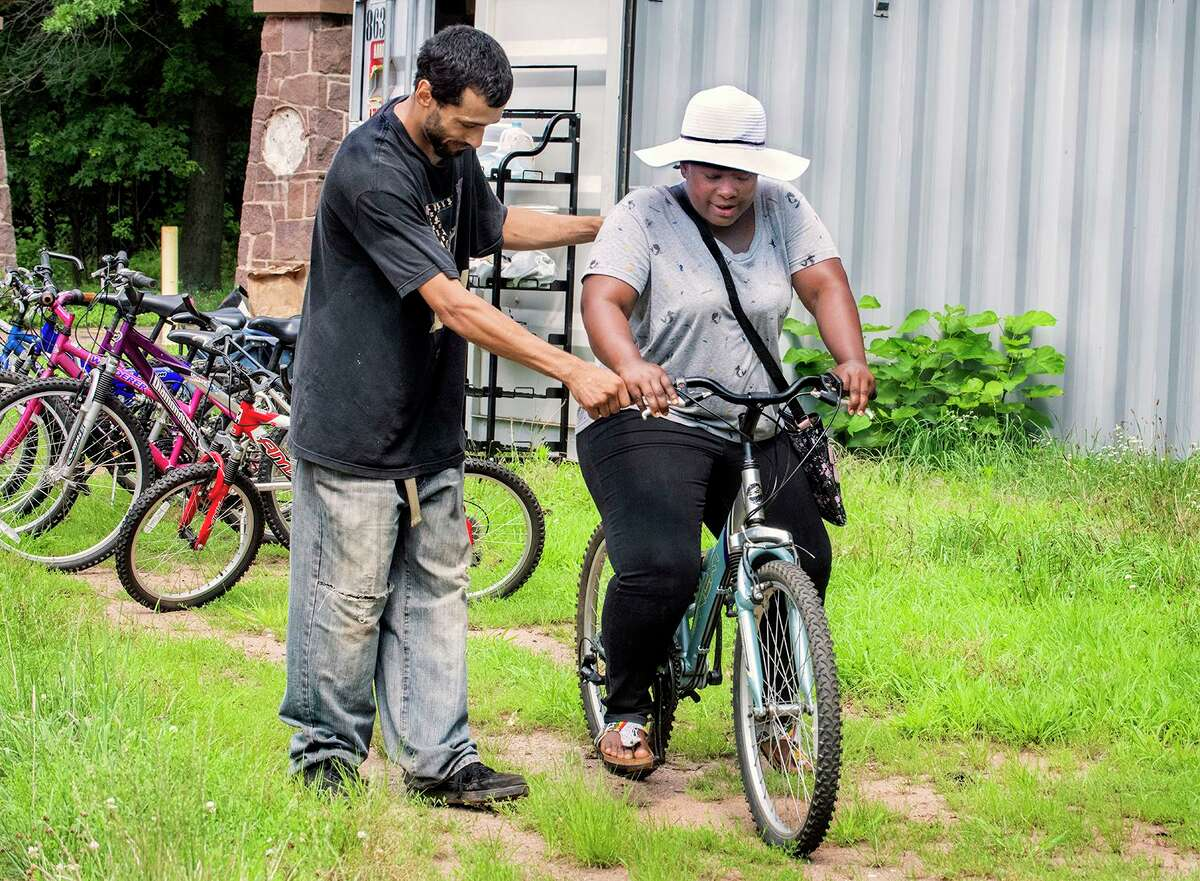 Alex Martinez, left, helps Salamatu Mohammed get started riding one of the bicycles provided for use by the Learning Corridor. Martinez is a Newhallville resident and works for the Community Placement Engagement Network.
