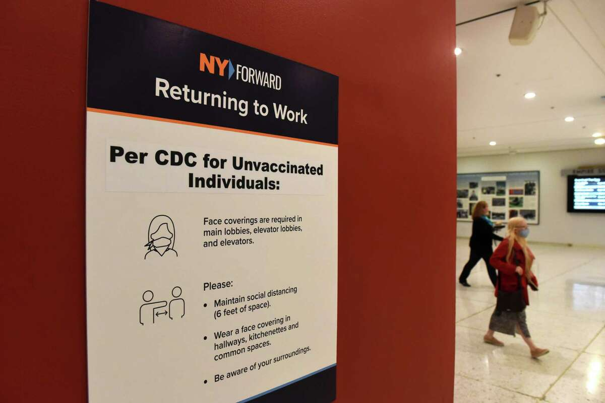 CDC guidelines for unvaccinated individuals are posted at entryways to the Empire State Plaza Concourse on Monday, Aug. 2, 2021, in Albany N.Y. Most counties in the Capital Region have hit a coronavirus transmission rate that, under CDC guidelines, triggers a recommendation that the unvaccinated and vaccinated wear masks indoors.
