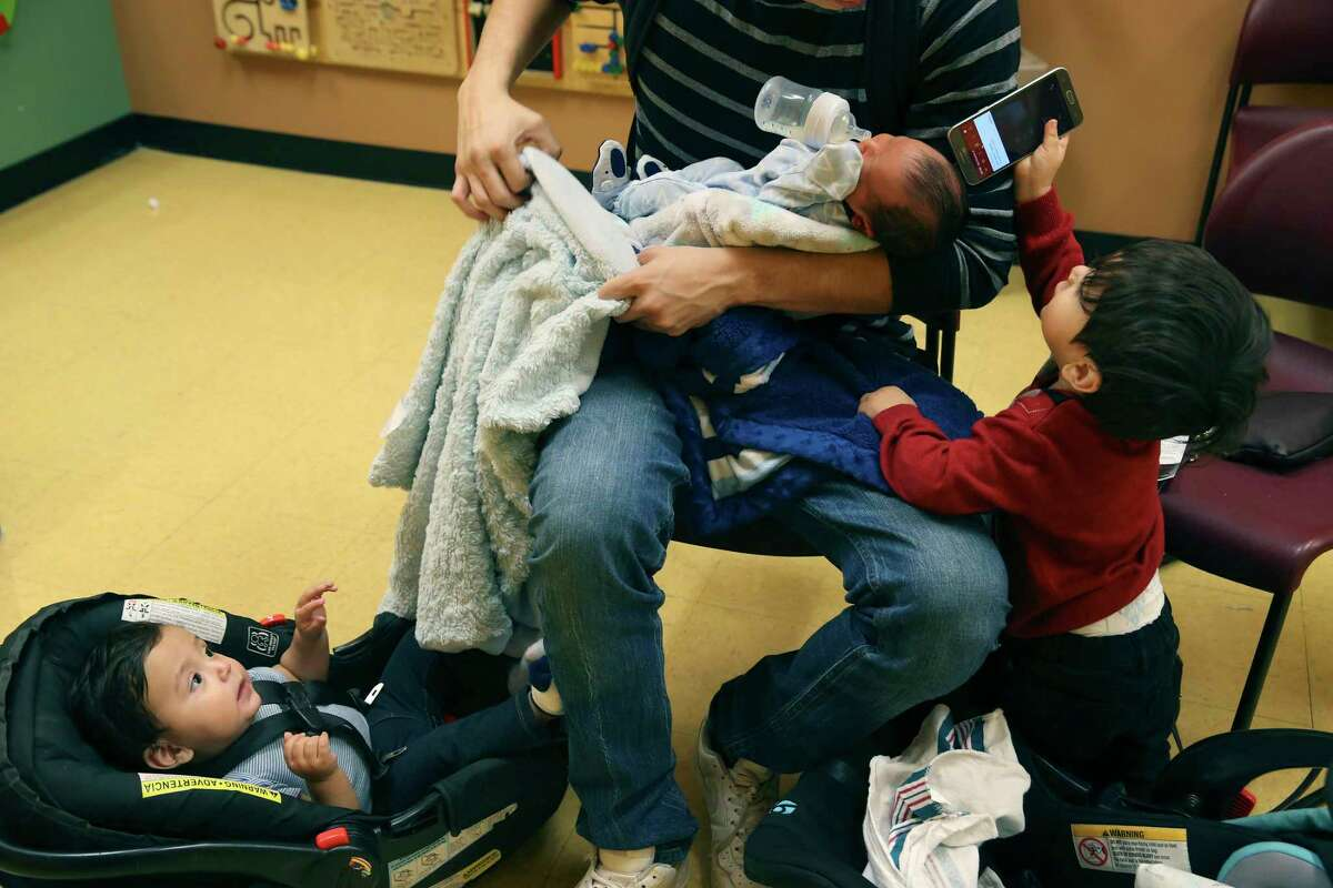 Eric Mora feeds his newborn son, Noah, as he sits with his other sons, Niovani, 1, left, and Eric Mora, Jr., 2, at the South Flores Women, Infant and Children Clinic, Wednesday, November 28, 2018. His wife, Adriana Rodriguez, was enrolling Noah, who was born on November 22nd in the program. Mora, a tile setter, said work is not consistent making it difficult for the family. According to a new report, one in five uninsured American children lives in Texas, the state with the highest number of children who lack coverage for basic health needs.