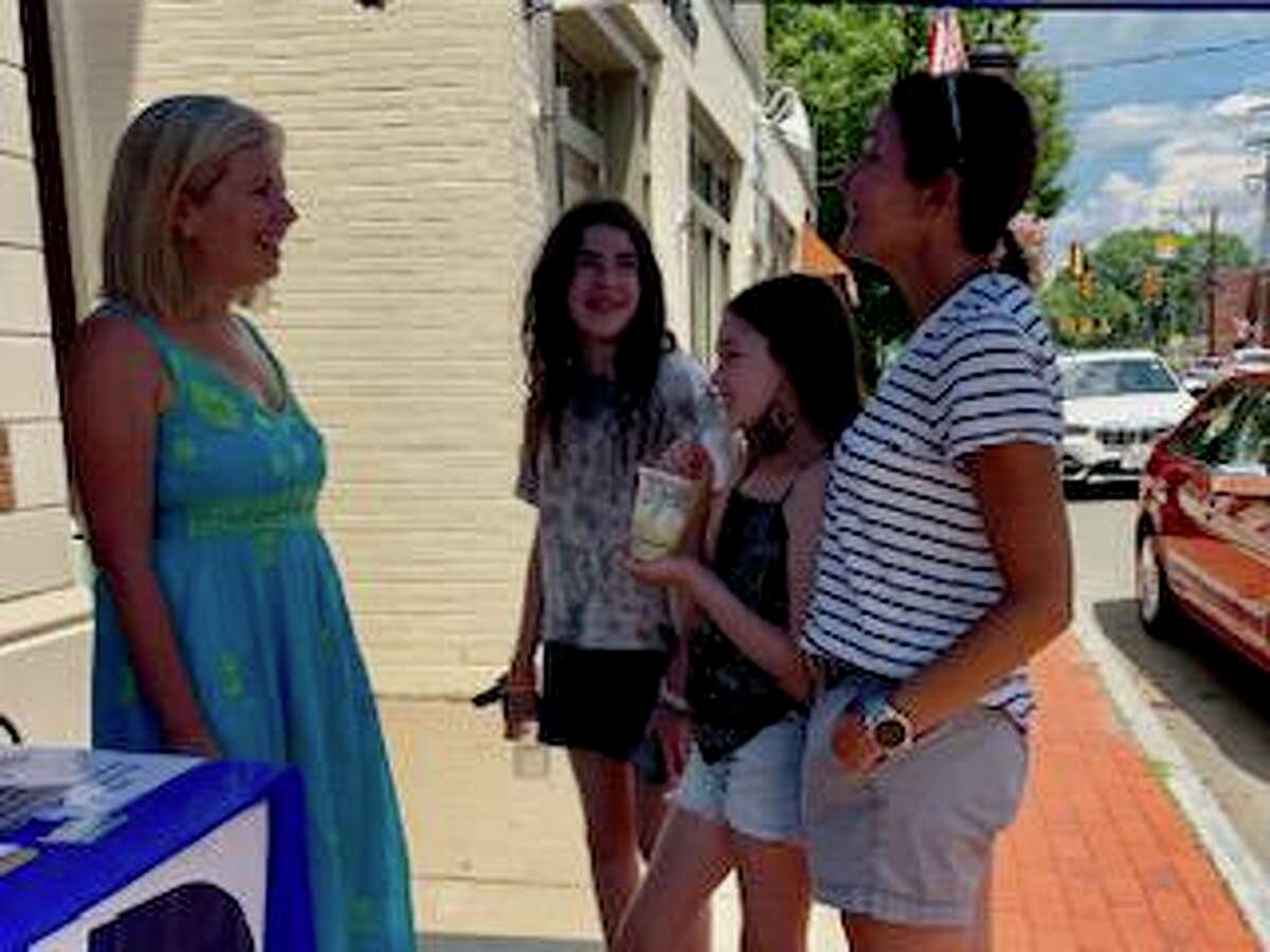 Darien Democratic first selectman candidate Tara Ochman talks with people during the Darien Sidewalk Sales Saturday, July 30, 2021. Ochman's booth was outside the former Brooks Brothers location.