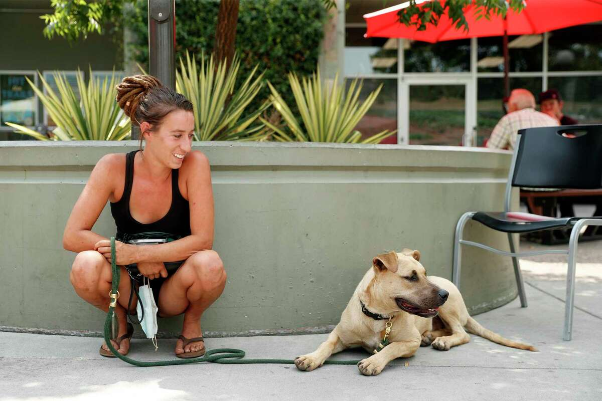 Grass Valley resident Emily Michaud watches Dune, a friend's dog, outside BriarPatch Food Co-op in Grass Valley, Calif., on Thursday, July 29, 2021.