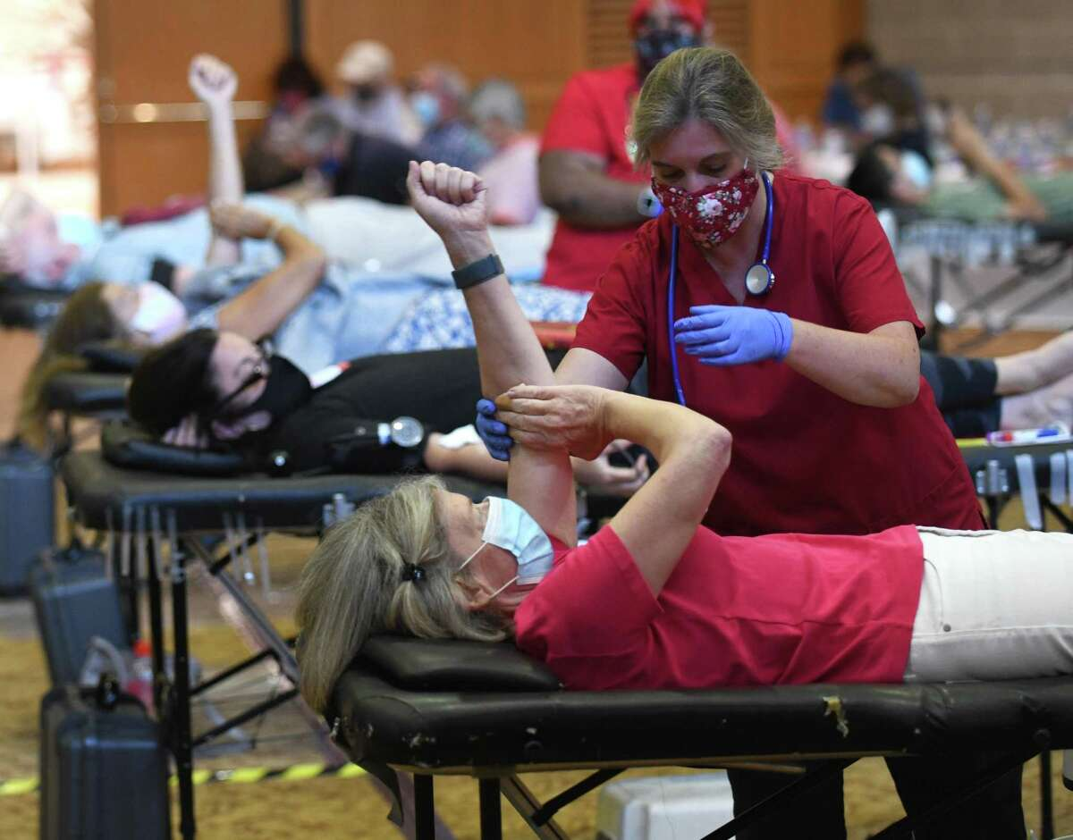 Collections technician Kelly Mohahan assists Sally Harris, of Greenwich, donating blood during the American Red Cross blood drive at Temple Sholom in Greenwich, Conn. Monday, Aug. 2, 2021. Considering COVID-19 precautions, blood donation appointments must now be booked in advance online, by calling 1-800-RED-CROSS, or using the American Red Cross app. The next American Red Cross blood drive in Greenwich will be at First Presbyterian Church on Aug. 20.