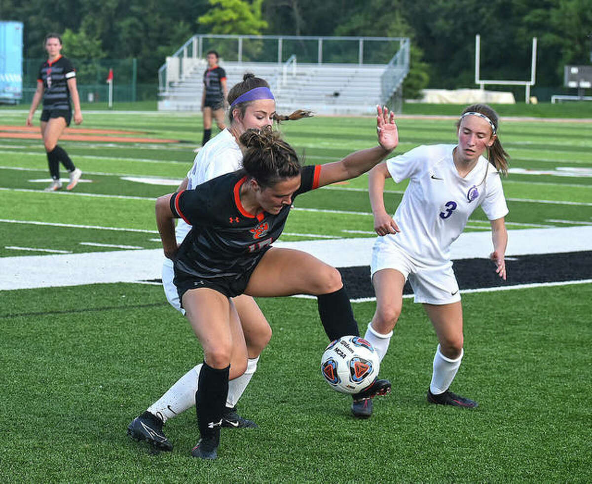 Edwardsville's Brynn Miracle, front, battles for position and the ball in the first half against Collinsville in a Class 3A regional championship game at the District 7 Sports Complex.