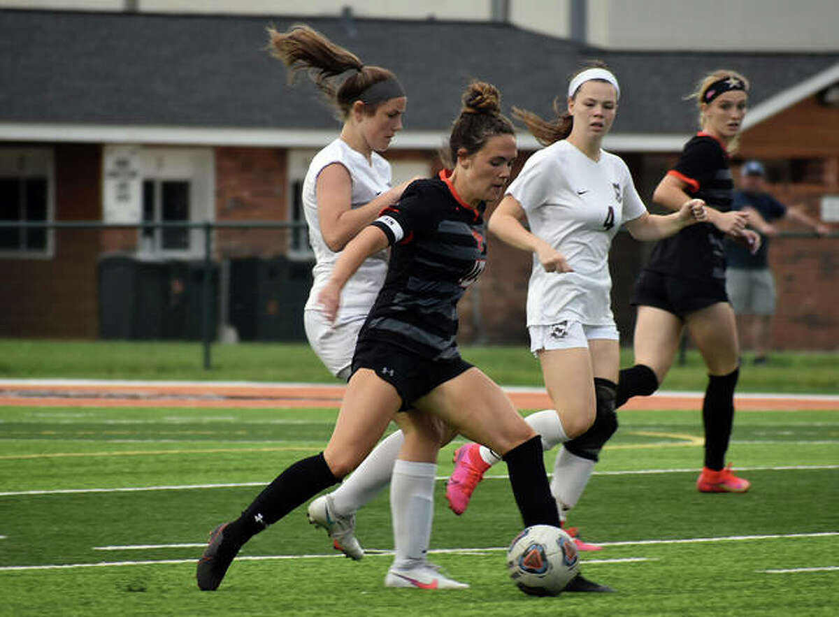 Edwardsville senior Brynn Miracle shields the ball away from Belleville West defenders while looking for an open teammate.