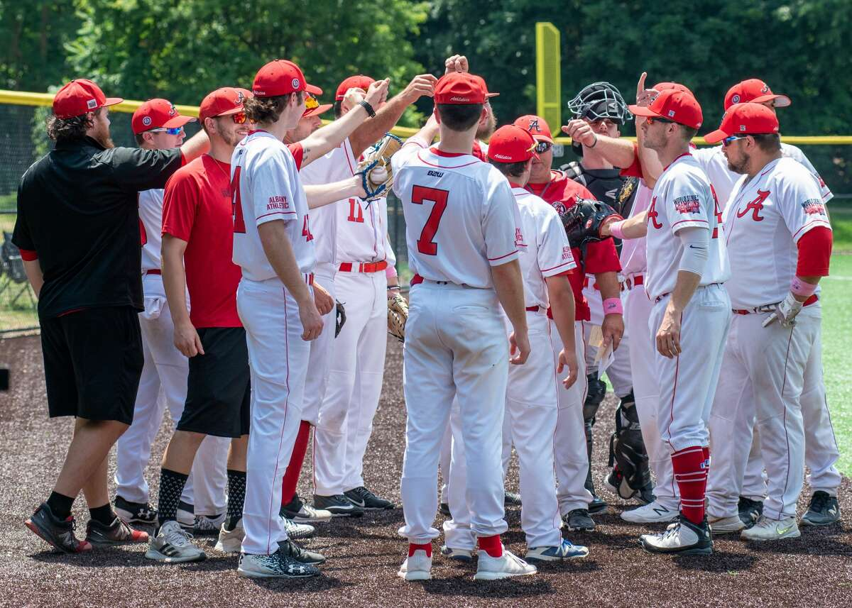 The Albany Athletics huddle before taking the field at a Central Park game in 2021.