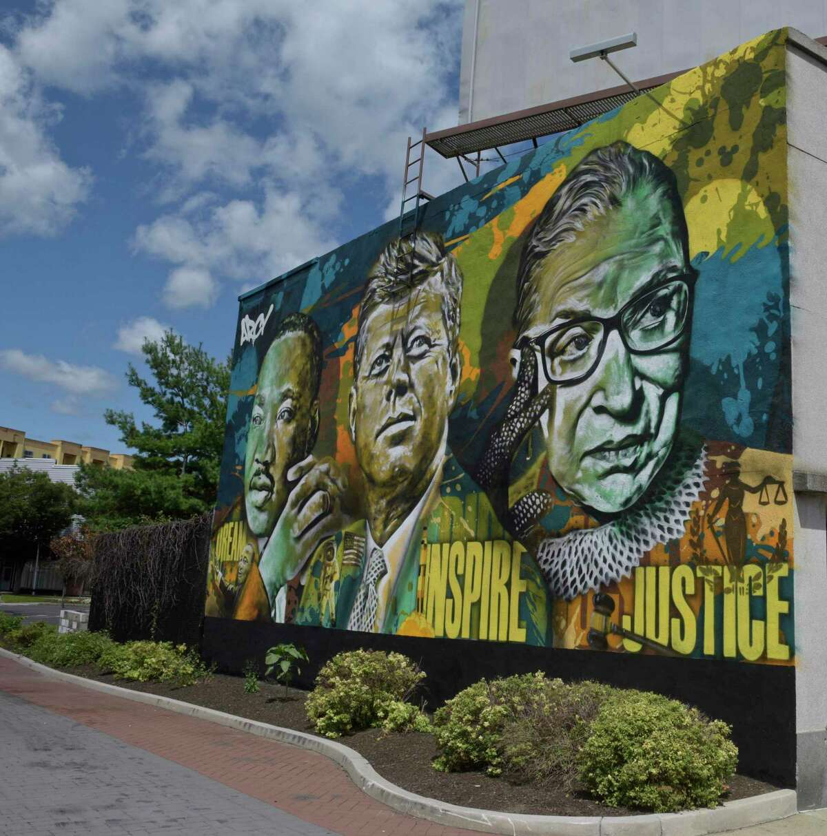 """Unveiling of mural of Martin Luther King Jr, John F. Kennedy and Ruth Bader Ginsburg by Connecticut artist Ryan Christenson, whose street name is """"ARCY"""", in Kennedy Park, Danbury, Conn. Monday, August 2, 2021."""
