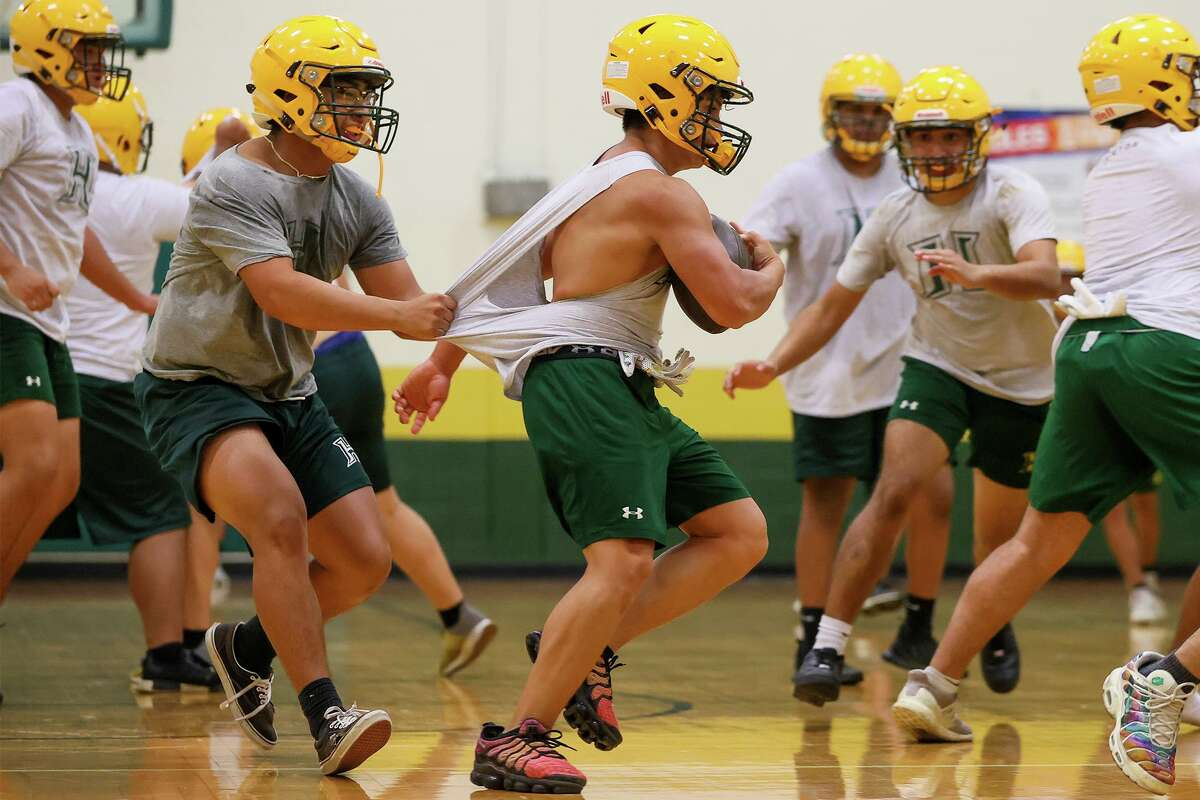 Holmes' defensive end Alex Brionas, left, tries to stop running back Joaquin Ramirez from behind during their first day of fall football practice, held in the school's gym due to heavy rain outside, on Monday, Aug. 2, 2021.