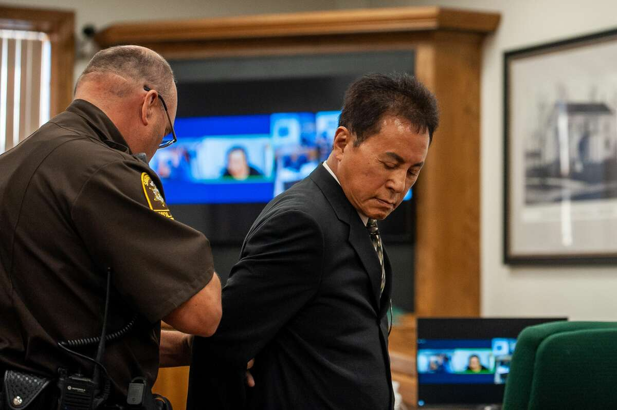 The owner of the old Holiday Inn, Jeff Kern, is handcuffed on Aug. 2, 2021 in a Midland County courtroom.