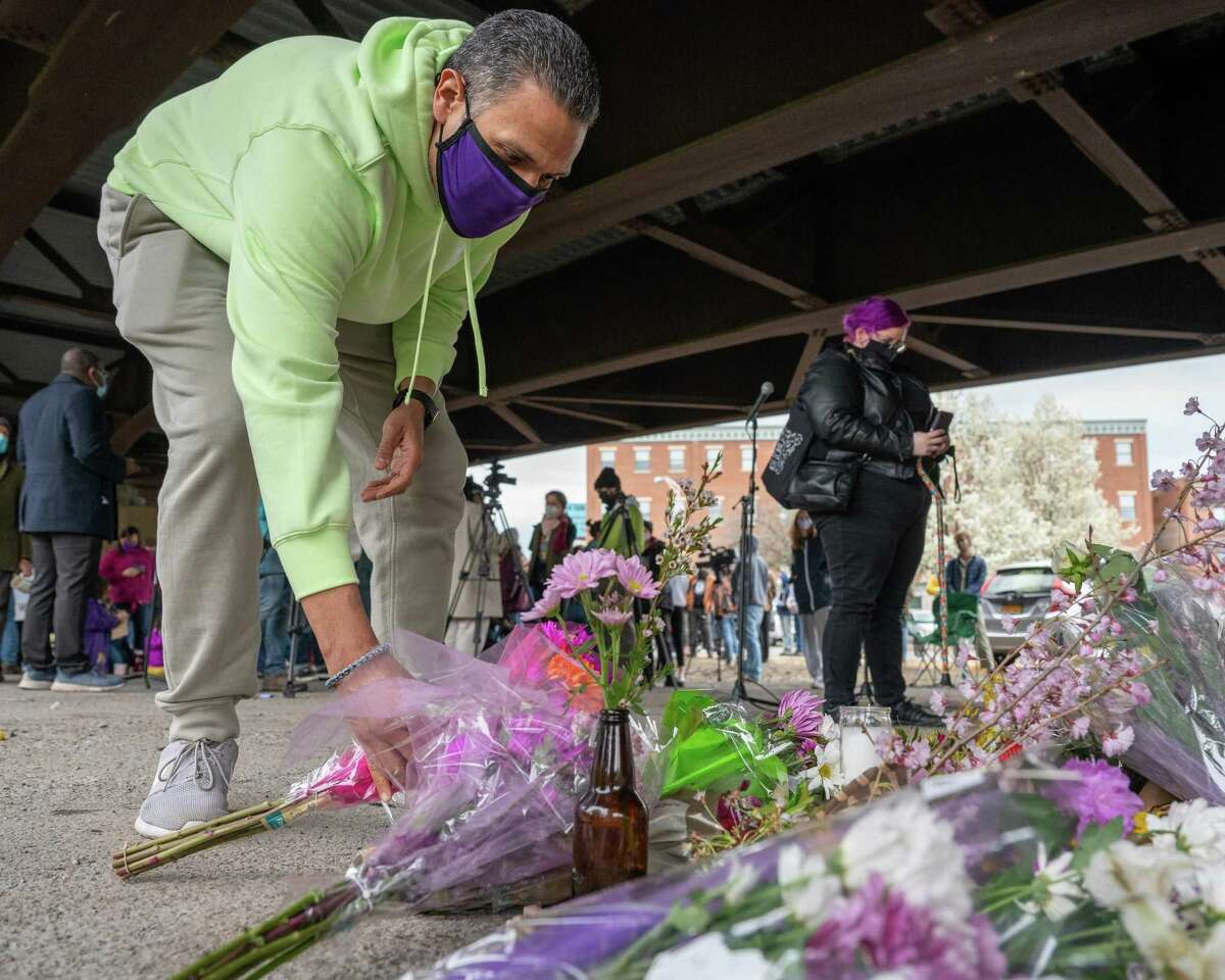 Elfredo Medina places flowers at a memorial during a rally commemorating the five-year anniversary of Edson Thevenin at the hands of Troy police. The rally, which was also a protest of how police treat people of color in Troy and beyond, was held under the Hoosick Street Bridge in Troy, NY, on Saturday, April 17, 2021. (Jim Franco/Special to the Times Union)