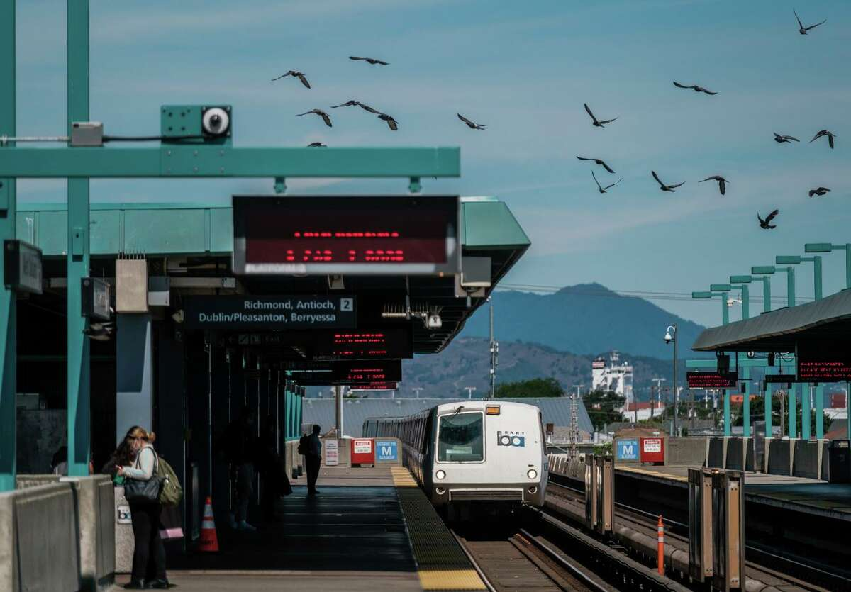 Riders are seen waiting for trains at the West Oakland BART Station in Oakland on Monday.