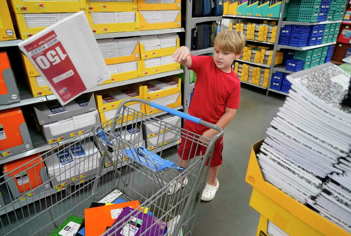 Third-grader Parker Stanton, 8, tosses a package of paper into the cart as he shops for school supplies with his mother at Walmart.