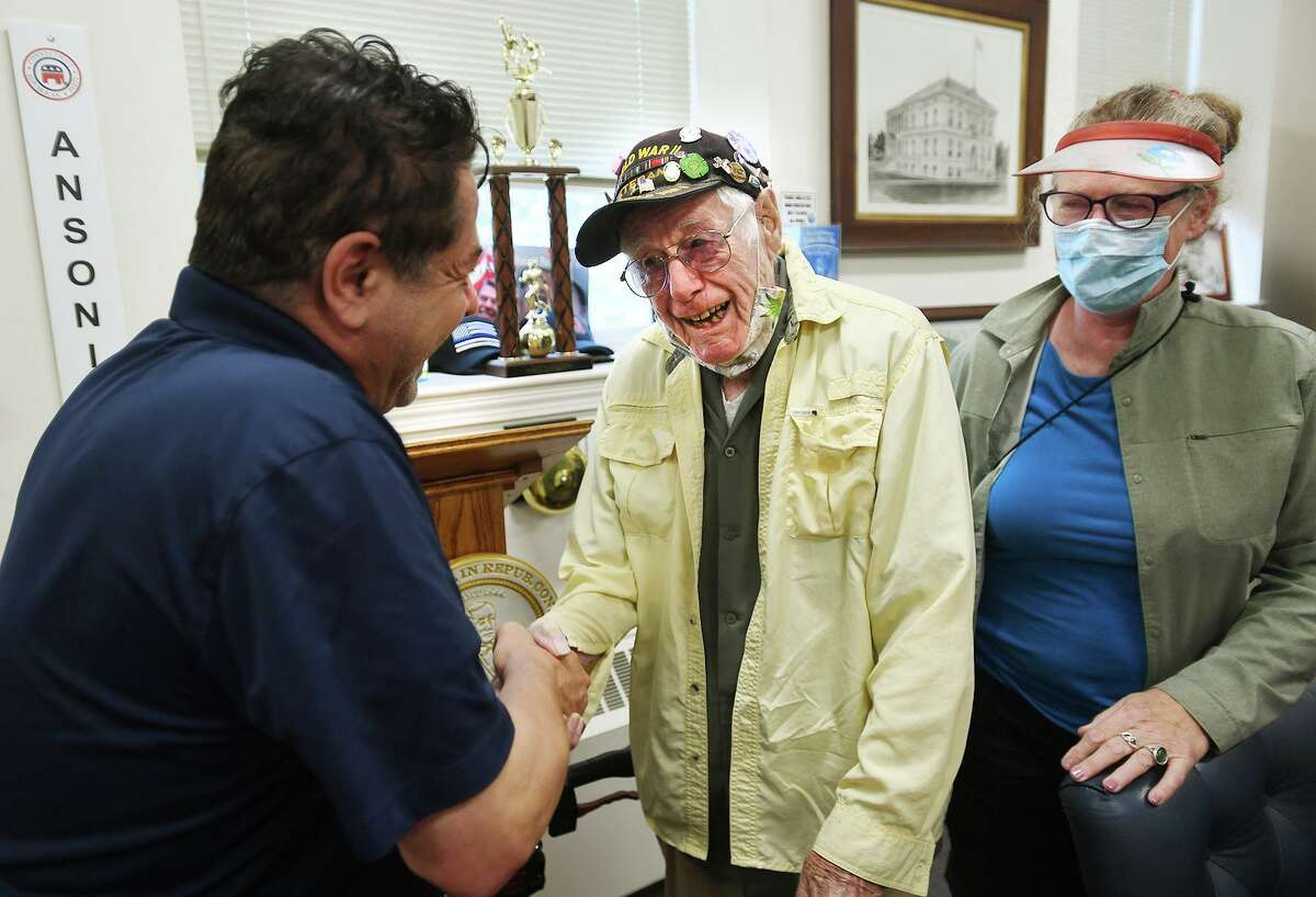 Mayor David Cassetti, left, greets World War 2 veteran Jay Murphy, 101, and his daughter Maryellen Murphy, during the reopening to the public of Ansoonia City Hall in Ansonia, Conn. on Monday, August 2, 2021. The Murphys, Ansonia natives who live in Redwing, MN, were revisiting the city for the first time since the pandemic.
