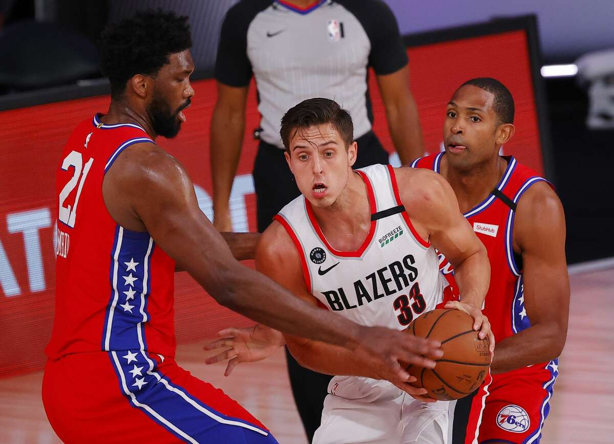 Zach Collins #33 of the Portland Trail Blazers is pressured by Joel Embiid #21 of the Philadelphia 76ers at Visa Athletic Center at ESPN Wide World Of Sports Complex on August 09, 2020 in Lake Buena Vista, Florida.