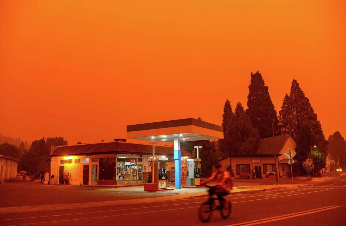 A man rides his bike past a gas station as smoke fills the sky from the Dixie fire in Greenville, California, on July 23, 2021. (Josh Edelson/AFP/Getty Images/TNS)