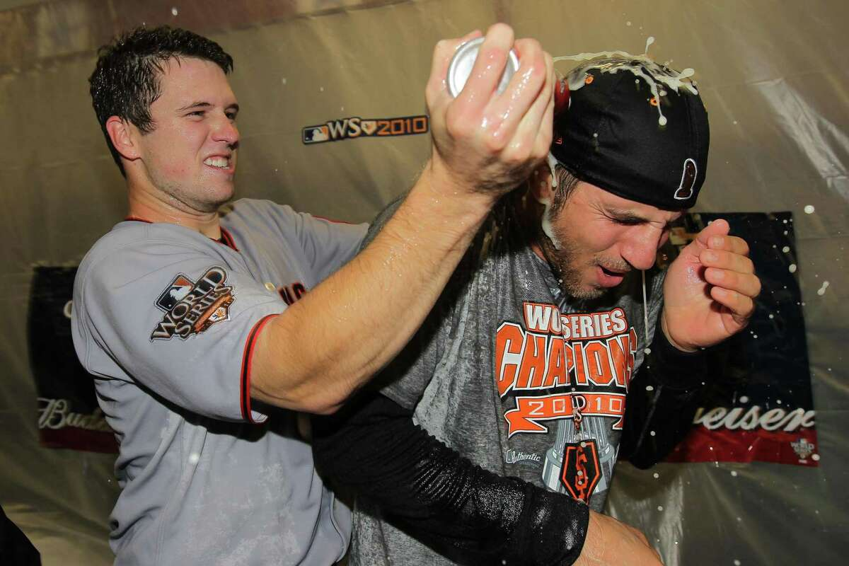 ARLINGTON, TX - NOVEMBER 01: Buster Posey #28 and Madison Bumgarner #40 of the San Francisco Giants celebrate in the locker room after the Giants won 3-1 against the Texas Rangers in Game Five of the 2010 MLB World Series at Rangers Ballpark in Arlington on November 1, 2010 in Arlington, Texas. (Photo by Doug Pensinger/Getty Images)