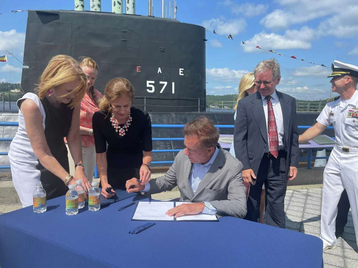 Gov. Ned Lamont signs a law that allows new residents, including military spouses, to receive the licenses and certifications necessary to practice in Connecticut, provided they are licensed in another state and have safely practiced for at least four years in front of the USS Nautilus in Groton on Monday.